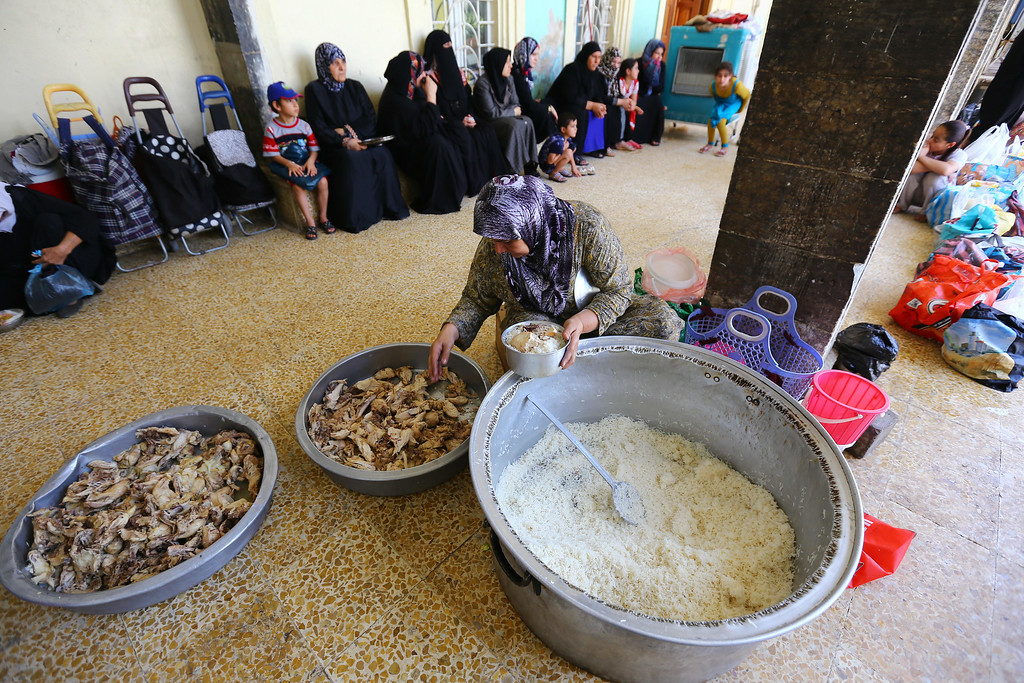 . Food is distributed in a mosque for displaced Iraqi families from Mosul and other areas, in Irbil, a city in the Kurdish controlled north 217 miles (350 kilometers) north of Baghdad, Iraq. Iraq\'s vice president called on parliament Thursday to convene next week, taking the first step toward forming a new government to present a united front against a rapidly advancing Sunni insurgency that threatens to spread across the region.(AP Photo)