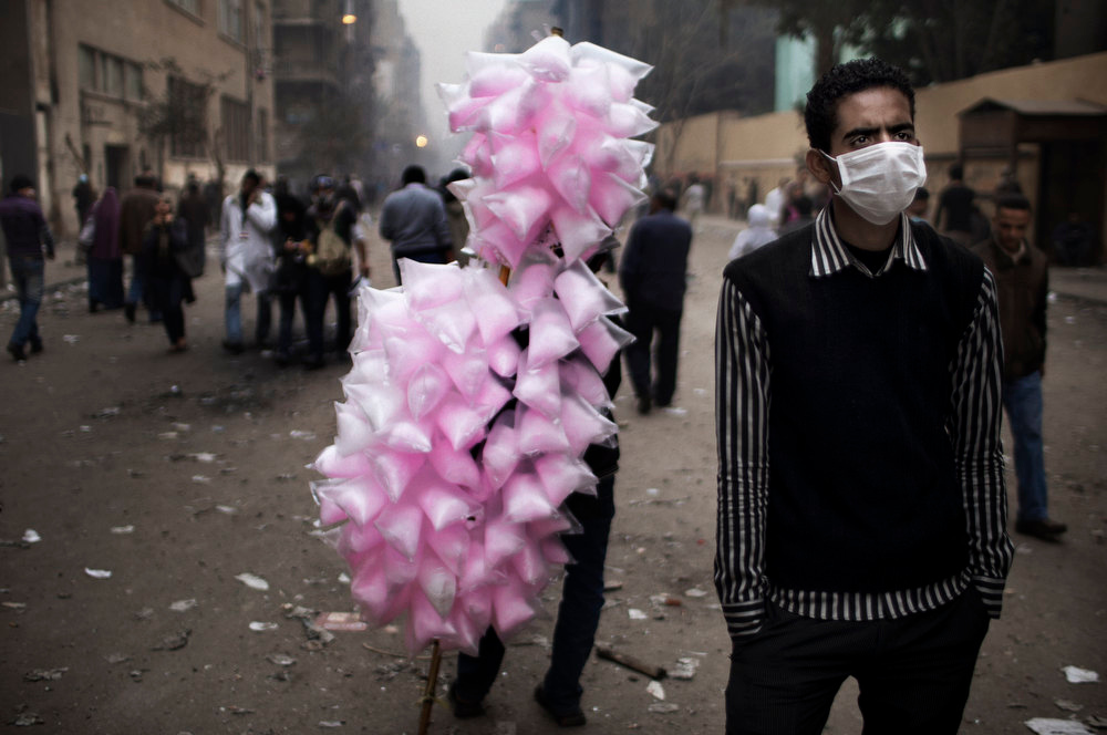 Description of . Standing next to a man selling cotton candy, an Egyptian demonstrator uses a protective mask against tear gas fired by riot police during confrontations outside Cairo's security headquarters on February 6, 2012, as clashes continued in the Egyptian capital in the wake of deadly football violence and amid calls by activists for civil disobedience in Egypt.   MARCO LONGARI/AFP/Getty Images