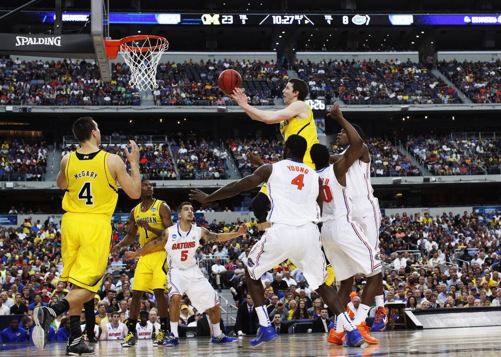 Description of . Nik Stauskas #11 of the Michigan Wolverines shoots over the Florida Gators in the first half during the South Regional Round Final of the 2013 NCAA Men\'s Basketball Tournament at Dallas Cowboys Stadium on March 31, 2013 in Arlington, Texas.  (Photo by Tom Pennington/Getty Images)