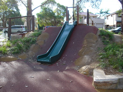 single green plastic slide on mound with softfall rubber and moulded boulders for clambering