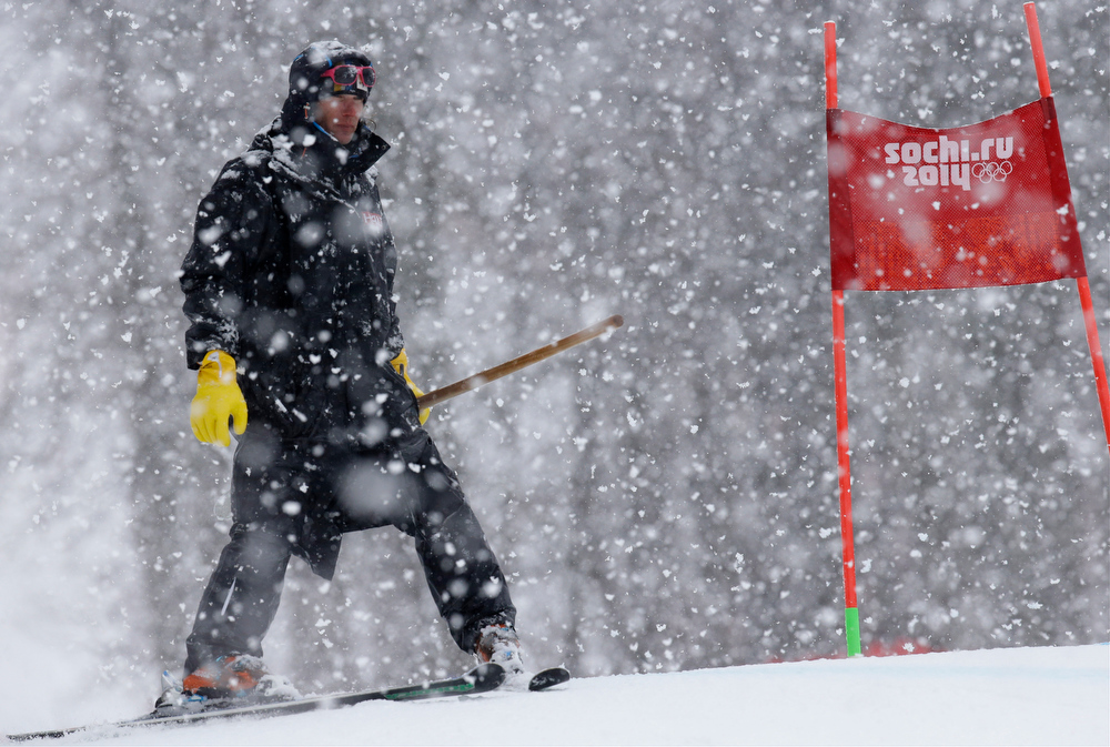 Description of . A ski course worker waits with a shovel under heavy snow fall just before the start of the second run of the women's giant slalom at the Sochi 2014 Winter Olympics, Tuesday, Feb. 18, 2014, in Krasnaya Polyana, Russia. (AP Photo/Luca Bruno)