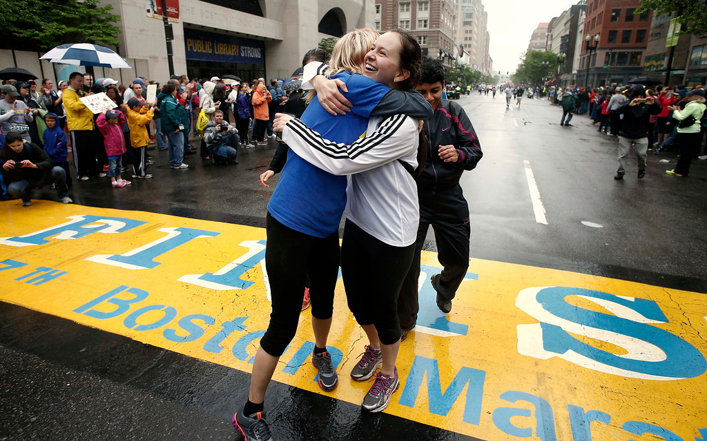 . Rachel, left, and Pam Vingsness of Newton, Mass., hug each other after crossing the finish line as runners who were unable to finish the Boston Marathon on April 15 because of the bombings were allowed to finish the last mile of the race in Boston, Saturday, May 25, 2013. (AP Photo/Winslow Townson)