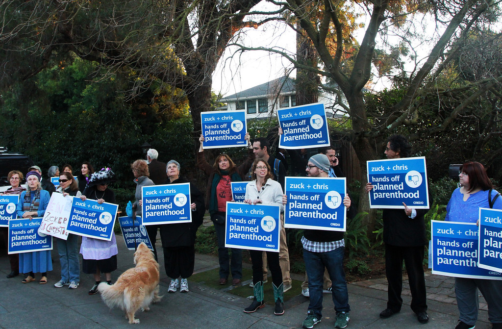 ". A group of protesters rally in front of the home of Facebook CEO Mark Zuckerberg in Palo Alto on Wednesday, Feb. 13, 2013. Zuckerberg hosted a campaign fundraiser for New Jersey Republican Gov. Chris Christie at his home Wednesday evening. About 40 protesters total demonstrated at the house; they said they were demonstrating against Christie�s visit because of his efforts to defund Planned Parenthood and other women�s reproductive health care programs. Protester and Palo Alto resident Cheryl Lilienstein said she wondered if Zuckerberg had any idea what Planned Parenthood means for women\'s health and Christie�s stances. ""I hope he\'s just confused,\"" she said. Zuckerberg and wife Priscilla Chan first got to know Christie after donating $100 million to struggling Newark schools two years ago, according to a Facebook spokeswoman.  (Kirstina Sangsahachart/ Daily News)"