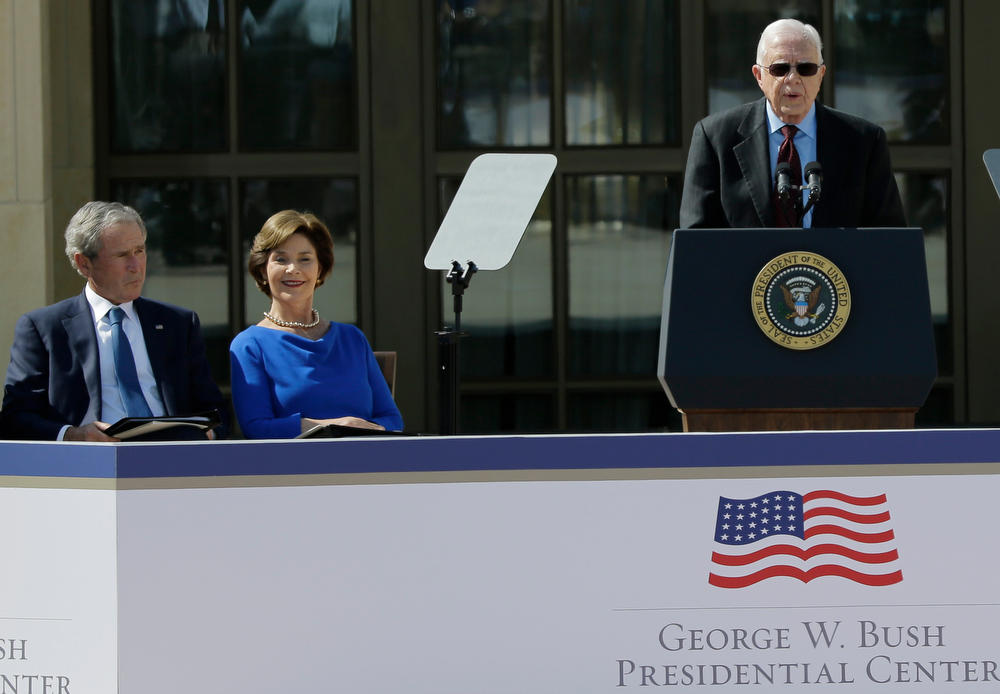Description of . Former president George W. Bush and his wife Laura Bush listen to former president Jimmy Carter during the dedication of the George W. Bush Presidential Center Thursday, April 25, 2013, in Dallas. (AP Photo/David J. Phillip)