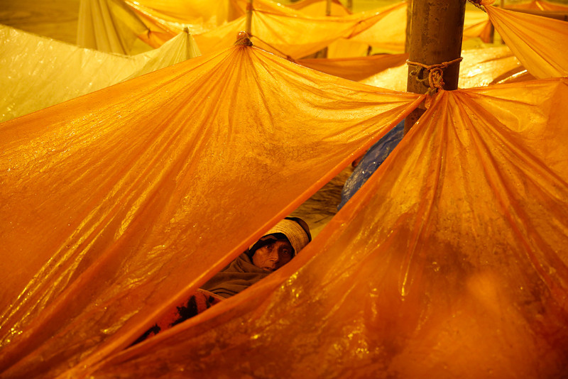 . Indian Hindu devotes rest beneath the temporary protection of plastic sheets at the Sangam, the confluence of rivers Ganges and Yamuna,on Mauni Amavasya, or new moon day, the third and the most auspicious date of bathing during the annual month long Hindu religious fair of Magh Mela in Allahabad, India,  Thursday, Jan. 30, 2014. Hundreds of thousands of Hindu pilgrims take dips in the confluence, some hoping to wash away sins and others to secure a fine spouse, during the month long festival. (AP Photo/Rajesh Kumar Singh)