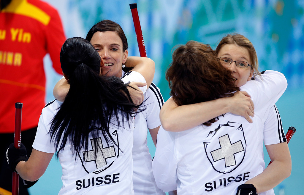 . Switzerlandís Carmen Schaefer, back to camera at left, hugs Carmen Kueng, and Mirjam Ott, back to camera at right, hugs Janine Greiner, after defeating China during women\'s curling competition at the 2014 Winter Olympics, Monday, Feb. 17, 2014, in Sochi, Russia. (AP Photo/Robert F. Bukaty)