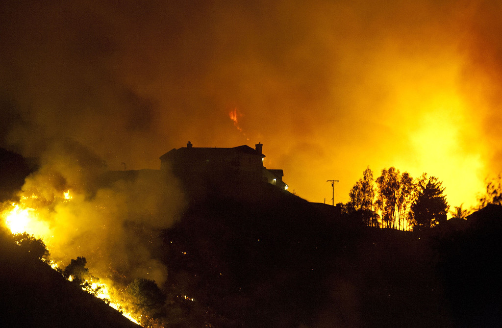 . A wildfire threatens homes in San Marcos, California, on May 15, 2014. Thousands of people fled raging wildfires in roasting southern California on Wednesday as flames destroyed homes and triggered evacuations at a nuclear power plant, a military base and an amusement park. The blazes, which also closed a major north-south highway, come amid record temperatures in the western US state, where the annual wildfire season typically starts much later in the year.   AFP PHOTO/JORGE CRUZ/AFP/Getty Images