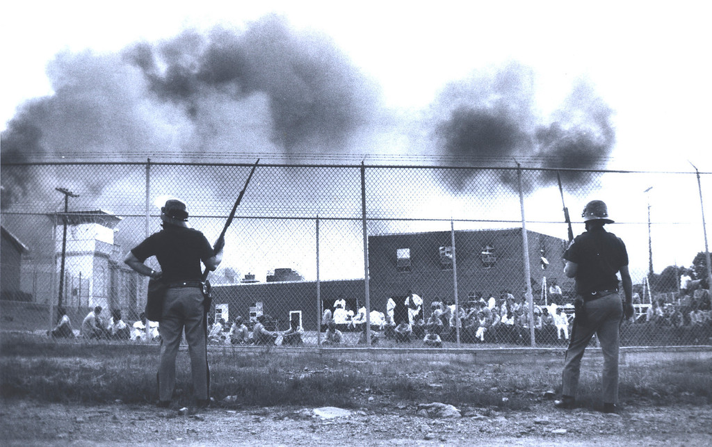 . In this July 1973 photo provided by the Oklahoma Department of Corrections, officials stand guard outside the fence of the Oklahoma State Penitentiary at McAlester in McAlester, Okla. during one of the most destructive prison riots in American history. The prison erupted into violence on July 27, 1973, the result of overcrowding, inadequate supervision, poor health care and a culture of violence within the prison walls. (AP Photo/Oklahoma Department of Corrections)
