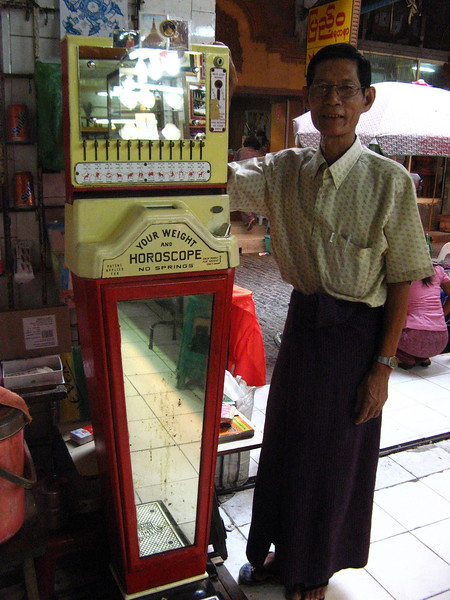 A man with his weight/horoscope machine at the Aung San Market