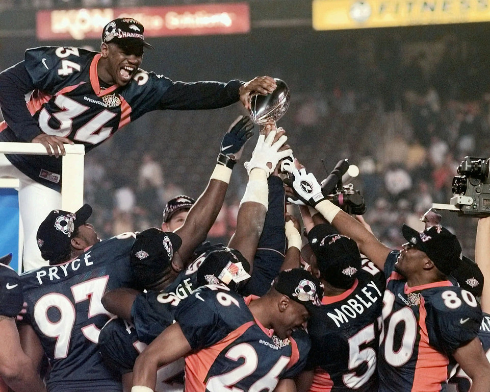 . Denver Broncos safety Tyrone Braxton (34) reaches out to touch the Vince Lombardi trophy held high by his teammates after Denver\'s 31-24 victory in Super Bowl XXXII at Qualcomm Stadium in San Diego Sunday, Jan. 25, 1998. (AP Photo/Ed Andrieski)