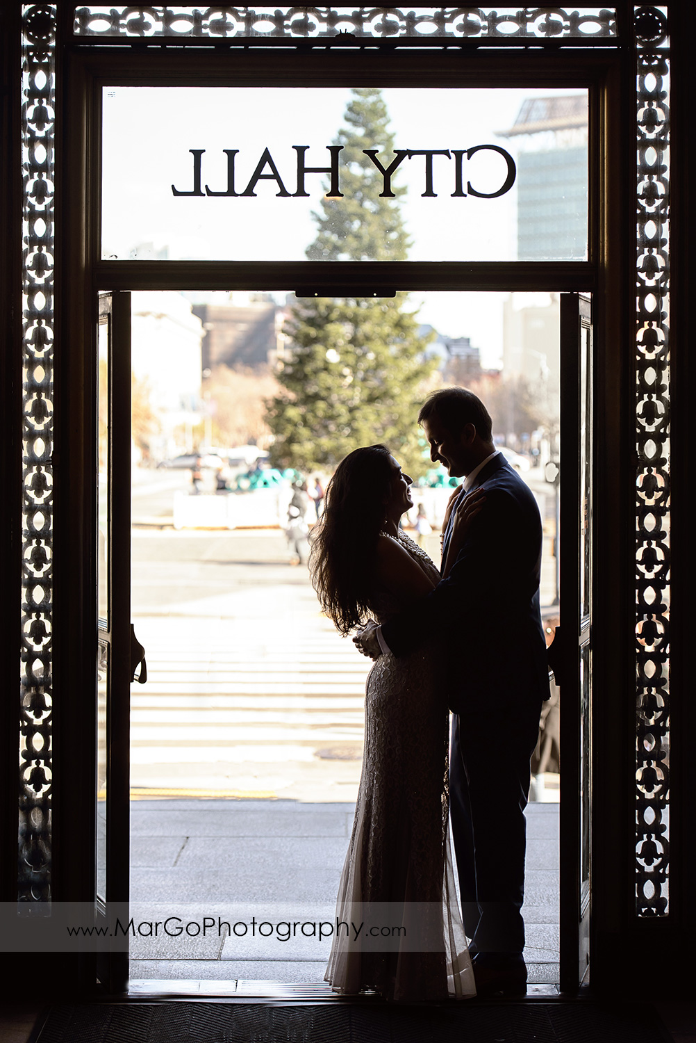 silhouette of the couple looking at each other in San Francisco City Hall entrance door