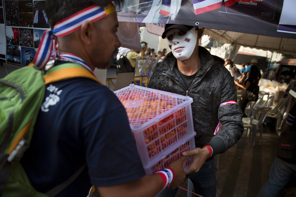 . An anti-government People\'s Democratic Reform Committee protester hands off a crate of fruit at an encampment in the Pathumwan district, Thursday, Jan. 16, 2014, in Bangkok. Anti-government protesters were on the march again in the Thai capital Thursday, targeting government offices they have not previous interfered with to keep up pressure on Prime Minister Yingluck Shinawatra to resign and call off next month\'s election. (AP Photo/John Minchillo)