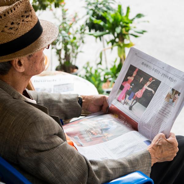 Man reading Korean newspaper, Seoul, South Korea