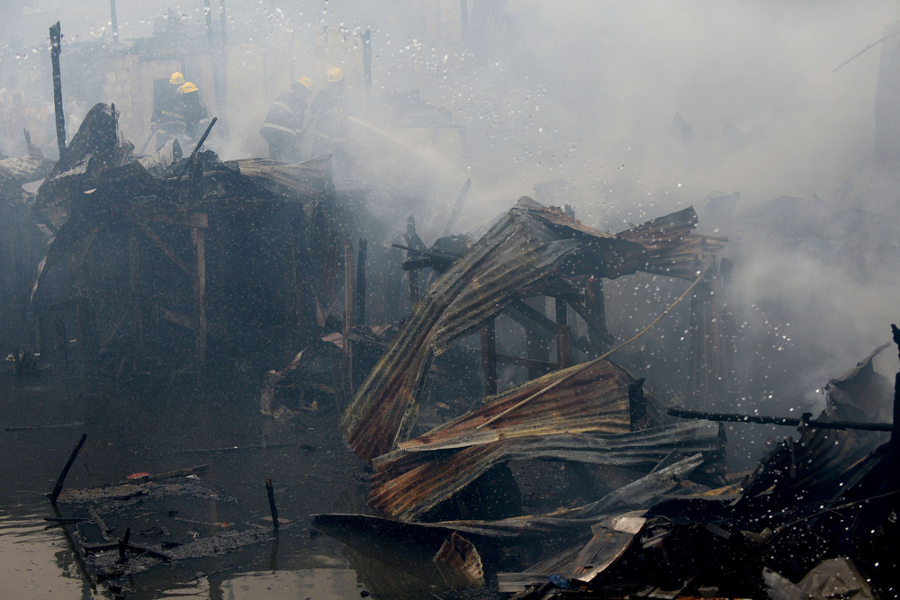 . Firemen (top L) spray water on a destroyed house after a fire razed a slum area beside a creek in Manila on July 24, 2013.  Almost 200 houses were destroyed, leaving 400 residents homeless, according to a local media report.  NOEL CELIS/AFP/Getty Images