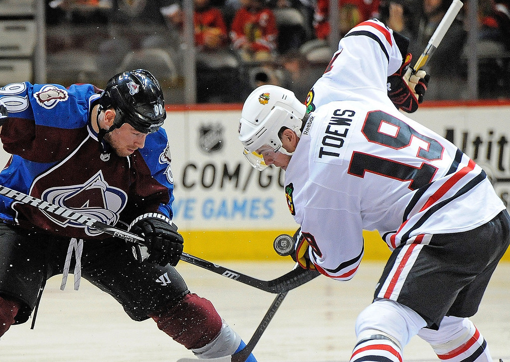 . Colorado Avalanche center Ryan O\'Reilly (90) and Chicago Blackhawks center Jonathan Toews (19) fight for the puck during the first period of an NHL hockey game, Monday, March 18, 2013, in Denver. (AP Photo/Jack Dempsey)