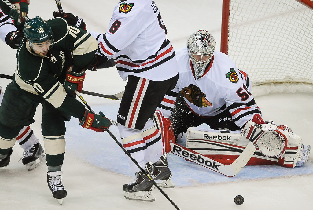 . Minnesota right wing Devin Setoguchi, left, takes a shot wide on goal around Chicago defenseman Nick Leddy, center and goalie Corey Crawford during the second period.  (Pioneer Press: Ben Garvin)