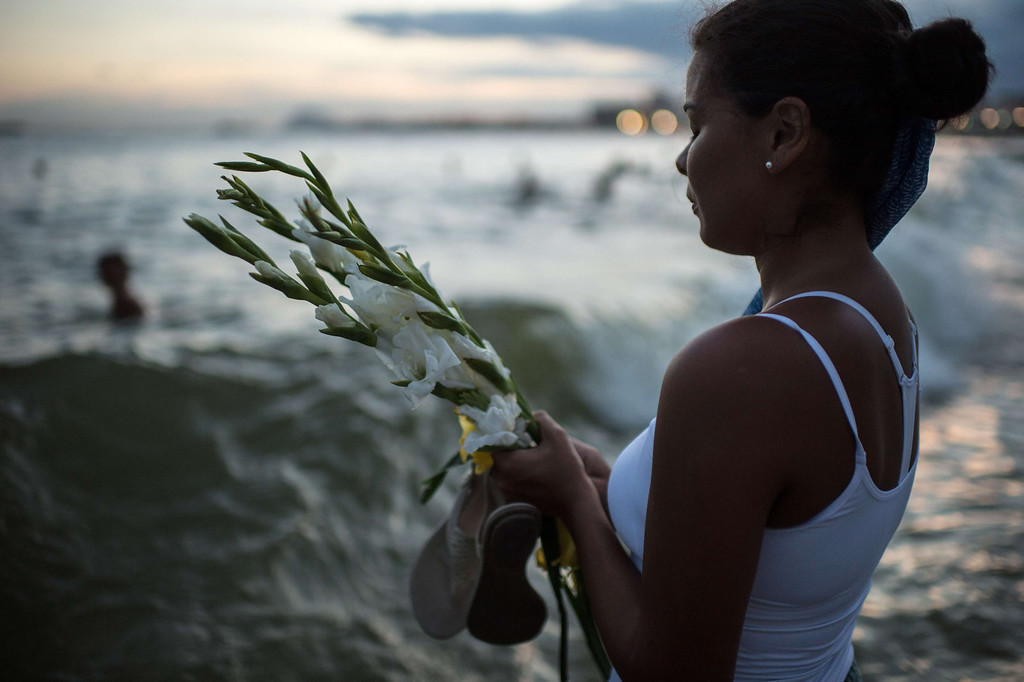 . A woman prays to the Yoruba goddess of the sea Yemanja at Copacabana beach in Rio de Janeiro, Brazil on December 31, 2013. YASUYOSHI CHIBA/AFP/Getty Images