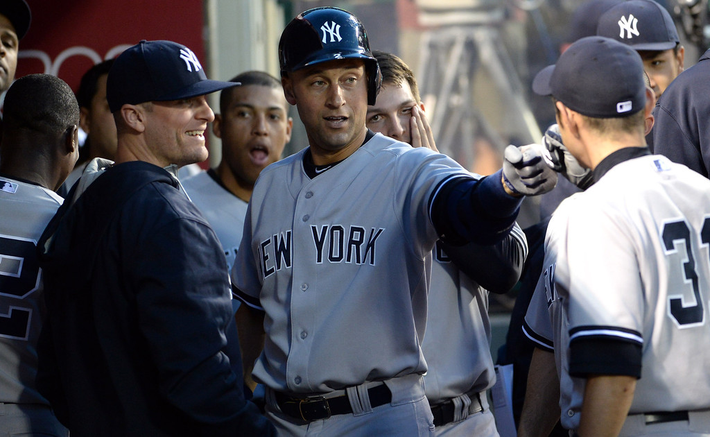. New York Yankees\' Derek Jeter high fives teammate after hitting a solo home run in the second inning of a baseball game against the Los Angeles Angels at Anaheim Stadium in Anaheim, Calif., on Wednesday, May 7, 2014.  (Keith Birmingham Pasadena Star-News)