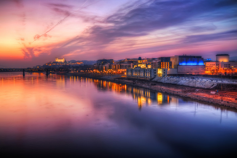 Lovely sunset  You get such a lovely view of the sunset from the bridges over Danube. So I always like to return there and take more photos. In this one, taken from the Apollo Bridge, you can see (from left) the Old Bridge, Bratislava Castle and the Eurovea shopping center. I'm really happy with the reflections, and that the shaking of the bridge had no impact on the shots.   HDR from three shots, taken with Canon 450D with Sigma 10-20mm lens, from a tripod.