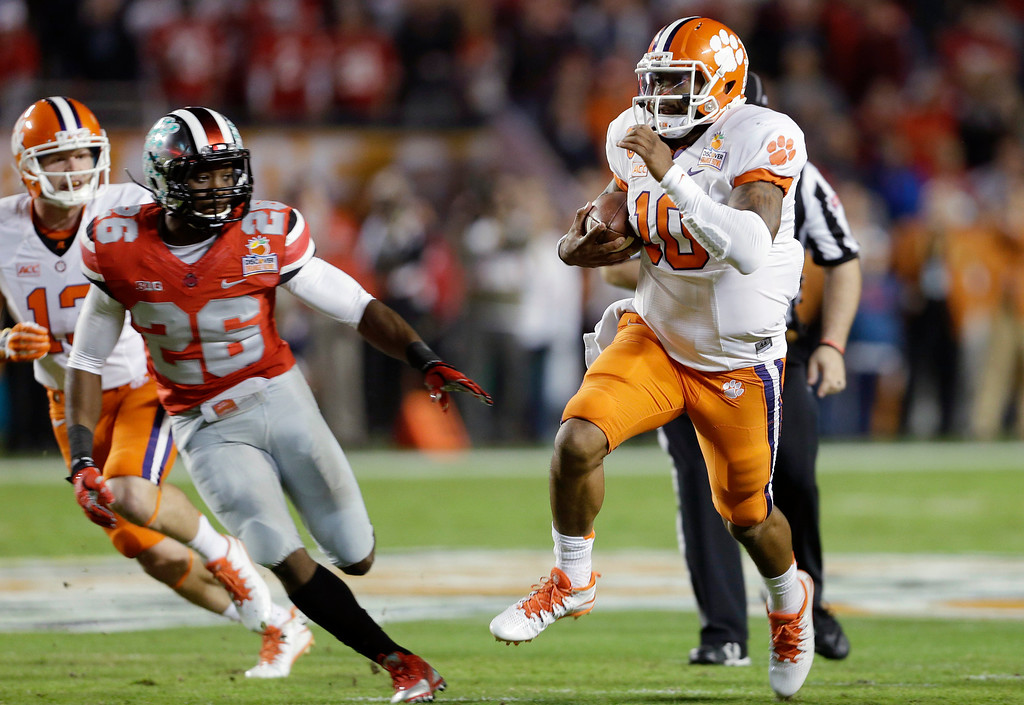 . Clemson quarterback Tajh Boyd (10) runs on his way to scoring a touchdown as Ohio State cornerback Armani Reeves (26) defends during the first half of the Orange Bowl NCAA college football game, Friday, Jan. 3, 2014, in Miami Gardens, Fla. (AP Photo/Lynne Sladky)