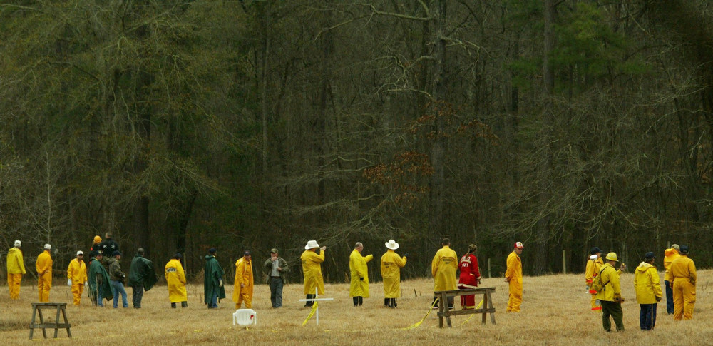 . Volunteers stand in a line less than 10 feet apart as they prepare to search a forest Monday, Feb. 3, 2003, outside Hemphill, Texas, where the body of a space shuttle Columbia astronaut was found over the weekend. (AP Photo/Dallas Morning News, Michael Mulvey)