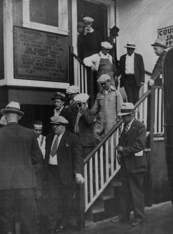 . OCT 22 1932  County Jail: One-Way Rides at the expense of Uncle Sam were taken by twenty-five convicted law violators, some of whom are shown below filing out of the Denver county jail. Most of the prisoners were sentenced to prison and reformatory terms by the United States district court here. The man with the light cap on the bottom step is Dorsey A. Trew, a former Jefferson county deputy sheriff, who must serve fifteen months in the federal prison at Leavenworth, Kan., for prohibition law violation. The prisoners left Denver Friday heavily guarded by United States deputy marshals. (Denver Post digital archive photo)