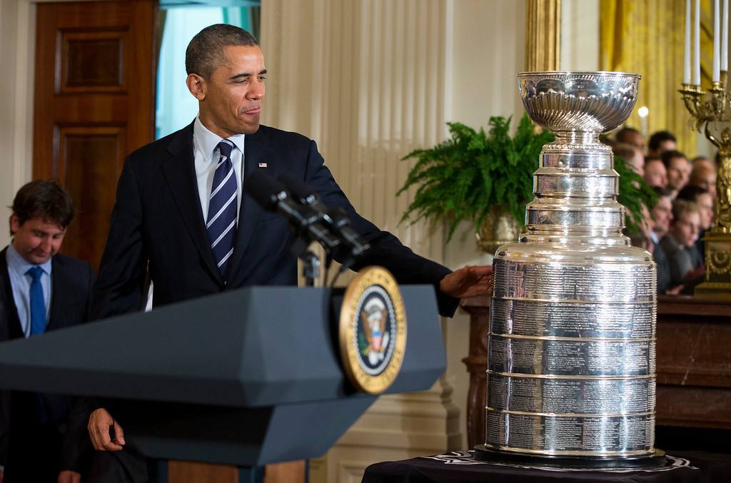 . President Barack Obama touches the Stanley Cup as he arrives for a ceremony to honor the NHL champion Chicago Blackhawks,  Monday, Nov. 4, 2013, in the East Room of the White House in Washington. (AP Photo/ Evan Vucci)