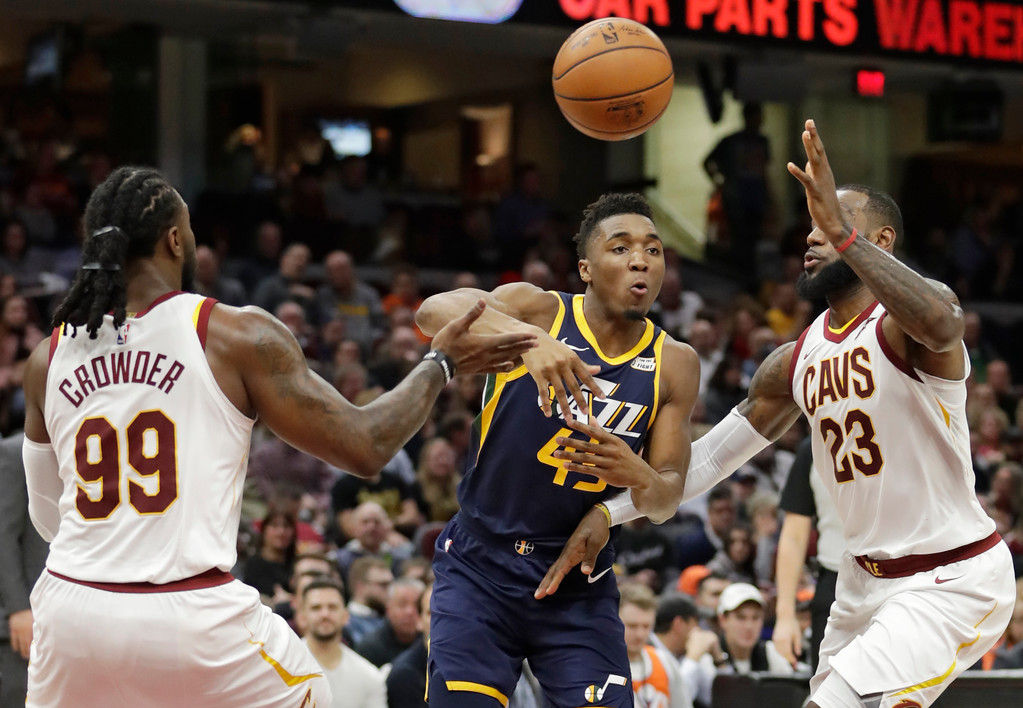. Utah Jazz\'s Donovan Mitchell (45) passes between Cleveland Cavaliers\' Jae Crowder (99) and LeBron James (23) in the first half of an NBA basketball game, Saturday, Dec. 16, 2017, in Cleveland. (AP Photo/Tony Dejak)