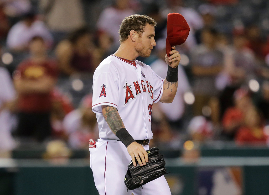 . Los Angeles Angels\' Josh Hamilton puts on his hat as he walks onto the field after the ninth inning of a baseball game against the Seattle Mariners in Anaheim, Calif., Tuesday, June 18, 2013. (AP Photo/Jae C. Hong)