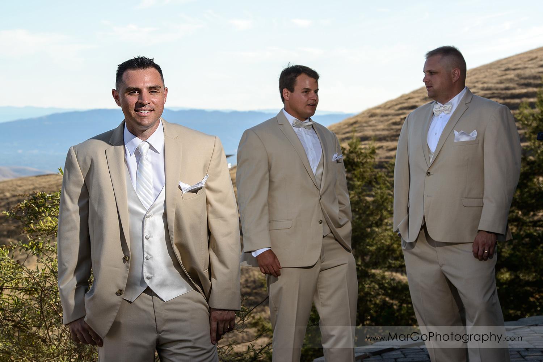 portrait of the groom in light suit with groomsmen in background