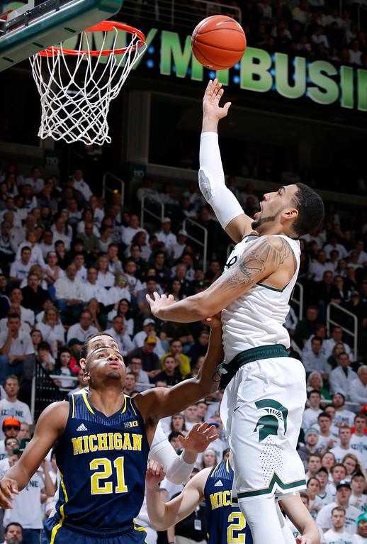 . Michigan State\'s Denzel Valentine, right, puts up a shot against Michigan\'s Zak Irvin (21) during the second half of an NCAA college basketball game, Sunday, Feb. 1, 2015, in East Lansing, Mich. Michigan State won 76-66 in overtime. (AP Photo/Al Goldis)