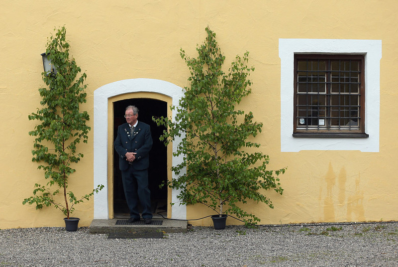 . A man looks outside at drizzling rain during the annual Corpus Christi (in German called Fronleichnam) mass at St. Michael\'s Church on May 30, 2013 in Seehausen am Staffelsee, Germany. The Seehausen Corpus Christi celebration usually includes a procession to a chapel across the nearby Staffelsee lake, though rain forced organizers to cancel the lake procession this year. Corpus Christi is among the highlights of the Catholic religious calendar in Bavaria.  (Photo by Sean Gallup/Getty Images)