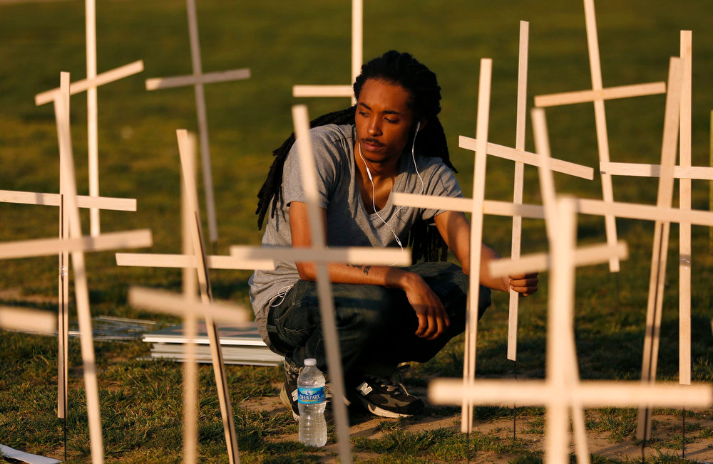 """. A volunteer places crosses symbolizing grave markers on the National Mall in Washington April 11, 2013. The PICO National Network\'s Lifelines to Healing and Sojourners are holding a 24-hour vigil featuring a gathering of Newtown clergy and 3,300 grave markers to \""""remind Congress action is needed on gun violence prevention.\"""" The number 3,300 represents the supposed number of people who have died as a result of gun violence since the tragedy in Newtown, Connecticut.  REUTERS/Kevin Lamarque"""