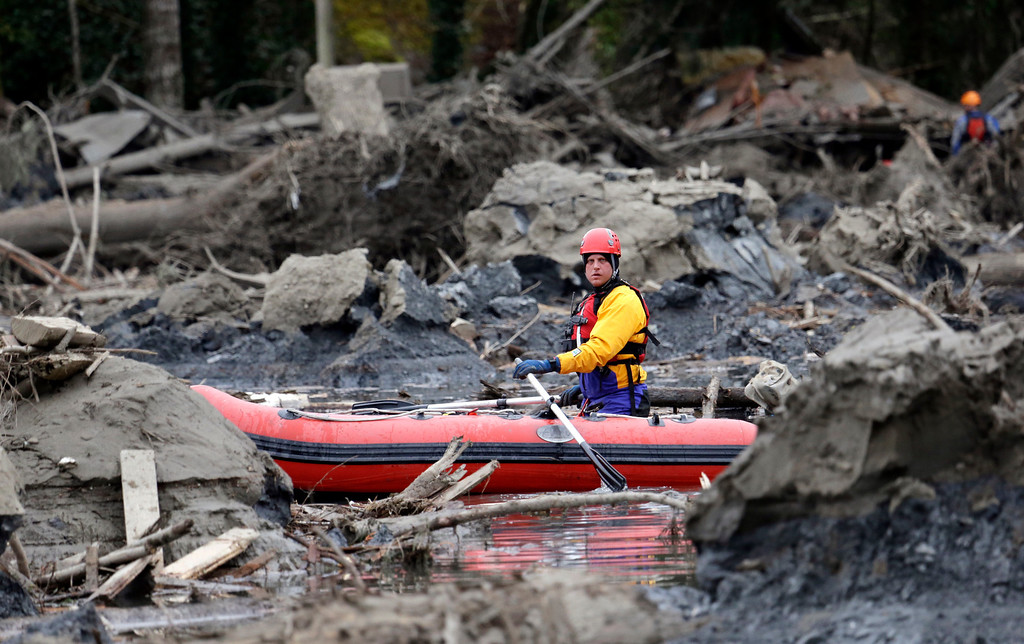 . A searcher uses a small boat to look through debris from a deadly mudslide Tuesday, March 25, 2014, in Oso, Wash. At least 14 people were killed in the 1-square-mile slide that hit in a rural area about 55 miles northeast of Seattle on Saturday. Several people also were critically injured, and homes were destroyed. (AP Photo/Elaine Thompson)