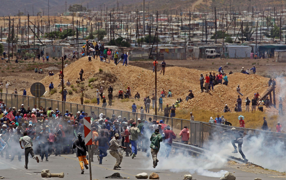 . Striking farm workers run away from South African Police after they fired tear gas at the demonstration in De Doorns , South Africa, Thursday, Jan 10, 2013. Striking farm workers in South Africa have clashed with police for a second day during protests for higher wages. The South African Press Association says police on Thursday fired rubber bullets at rock-throwing demonstrators in the town of De Doorns in Western Cape province, and protests were occurring in at least two other towns. (AP Photo/Schalk van Zuydam)