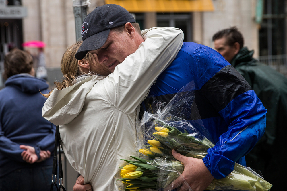 . A man and woman embrace after the ceremony commemorating the one year anniversary of the 2013 Boston Marathon Bombing, on April 15, 2014 in Boston, Massachusetts. Last year, two pressure cooker bombs killed three and injured an estimated 264 others during the Boston marathon, on April 15, 2013. Neary says she was standing near the site of the bombing before it went off.  (Photo by Andrew Burton/Getty Images)