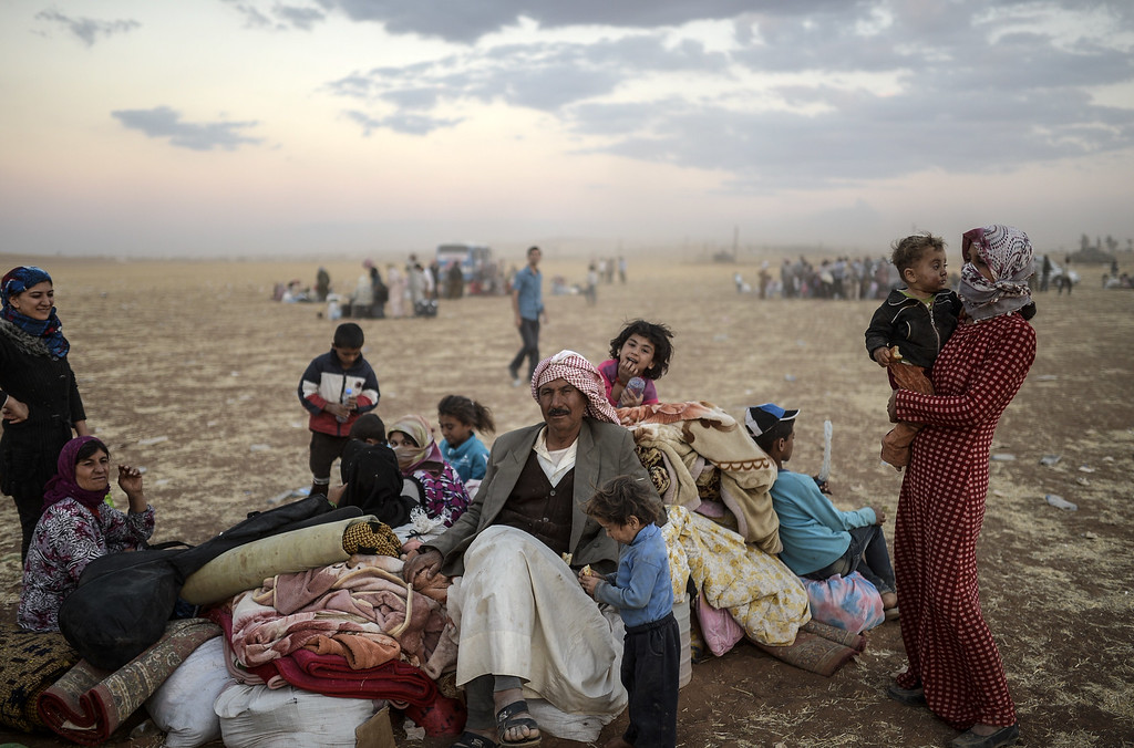 . Syrian Kurds wait near the Syrian border at the southeastern town of Suruc in Sanliurfa province, on September 20, 2014. Tens of thousands of Syrian Kurds flooded into Turkey on Saturday, fleeing an onslaught by the jihadist Islamic State group that prompted an appeal for international intervention.  BULENT KILIC/AFP/Getty Images