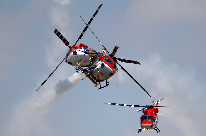 . Indian Air Force helicopters cross paths while performing an aerobatic flight on the opening of the Aero India 2013 at Yelahanka air base in Bangalore, India, Wednesday, Feb. 6, 2013. More than 600 aviation companies along with delegations from 78 countries are participating in the five-day event that started Wednesday. (AP Photo/Aijaz Rahi)