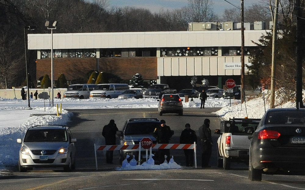 . A police road block is at the entrance to the new Sandy Hook Elementary School on the first day of classes in Monroe, Conn., Thursday, Jan. 3, 2013. The school, formerly known as Chalk Hill School, was overhauled specially for the students from the Sandy Hook School shooting in Newtown, in the neighboring town of Monroe, Conn. (AP Photo/Jessica Hill)