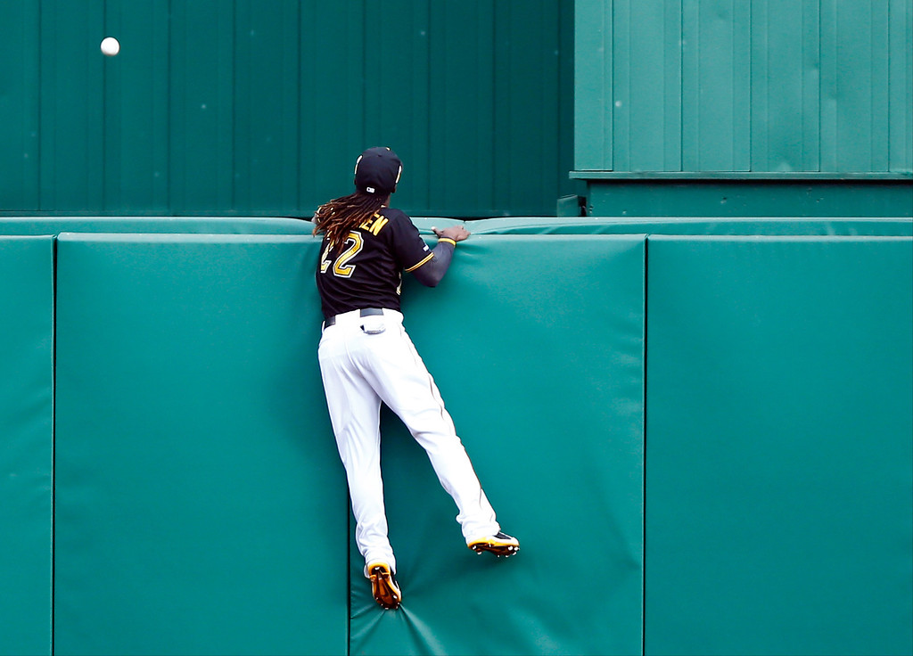 . Andrew McCutchen #22 of the Pittsburgh Pirates climbs the wall in attempt to catch Matt Holliday #7 of the St. Louis Cardinals two run home run against Charlie Morton #50 of the Pittsburgh Pirates in the sixth inning during Game Four of the National League Division Series at PNC Park on October 7, 2013 in Pittsburgh, Pennsylvania.  (Photo by Justin K. Aller/Getty Images)