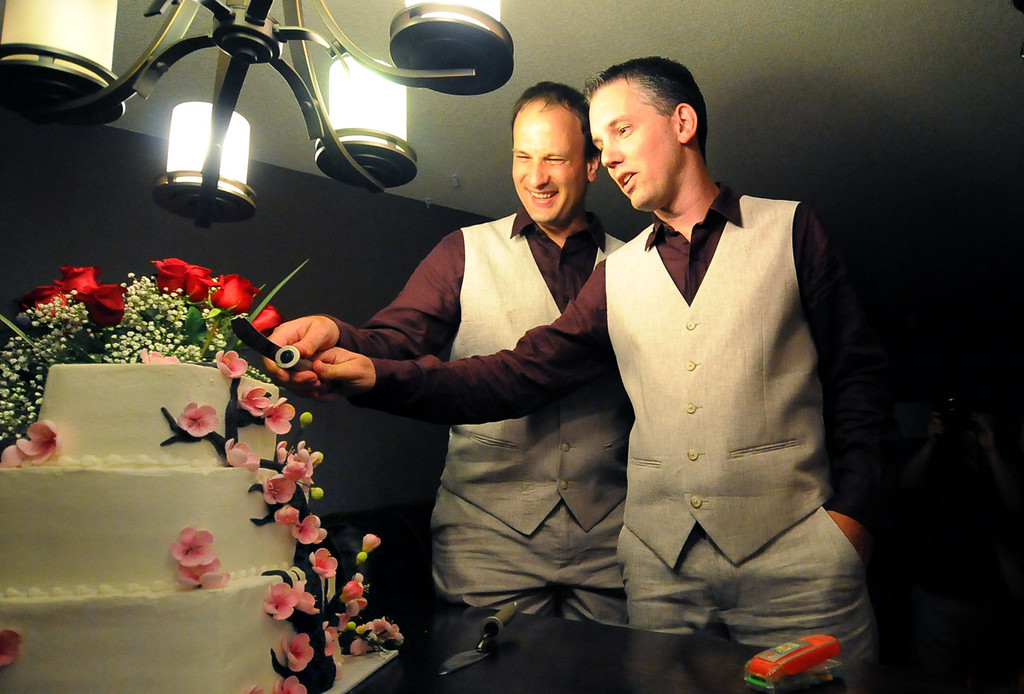 . Bradley Weber, left, and Ryan Pfeifle begin cutting their cake at a pre-wedding party at their home in Eden Prairie on Wednesday, July 31, 2013. The two are among the first couples in Minnesota that legally wed under the state\'s new Marriage Equality Act.  (Pioneer Press: Sherri LaRose-Chiglo)