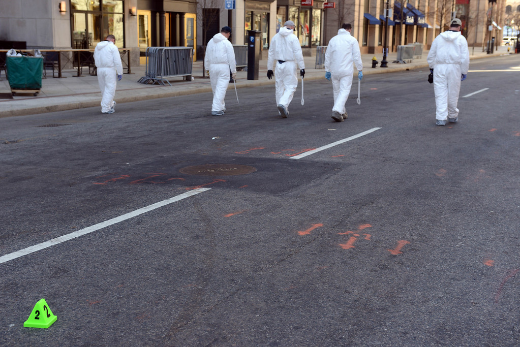 . FBI crime scene investigators sweep up Boylston Street after placing an evidence marker down just past Berkeley Street April 17, 2013 in Boston, Massachusetts.   Investigators continue to work the scene of two bomb explosions at the finish line of the marathon that killed 3 people and injured over one hundred more. (Photo by Darren McCollester/Getty Images)