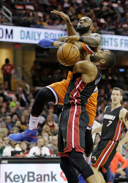 . Cleveland Cavaliers\' LeBron James, left, is fouled by Miami Heat\'s Wayne Ellington in the first half of an NBA basketball game Friday, Dec. 9, 2016, in Cleveland. (AP Photo/Tony Dejak)