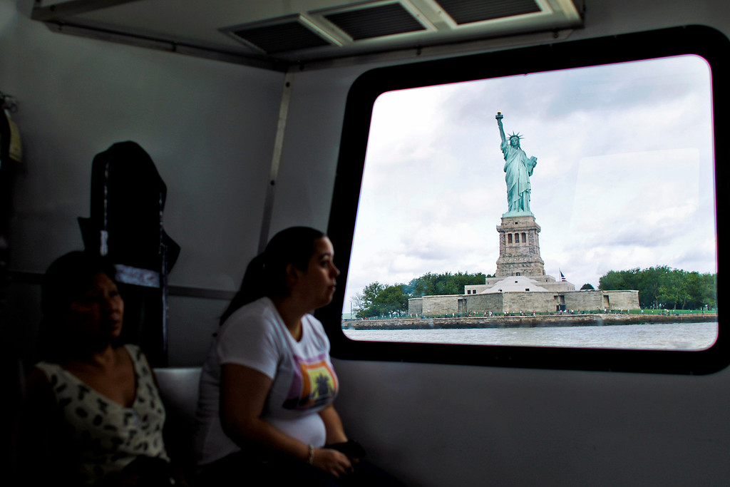 . People ride a ferry to visit the Statue of Liberty and Liberty Island during its reopening to the public in New York, July 4, 2013. Under steamy summer skies, tourists in New York flocked to ferries headed for the Statue of Liberty, re-opening with an Independence Day ceremony after closing in October as Superstorm Sandy approached.  REUTERS/Eduardo Munoz