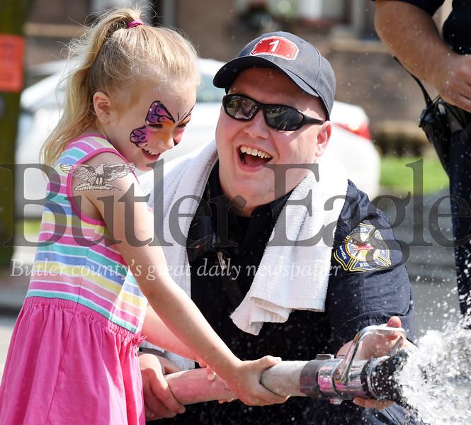 Harold Aughton/Butler Eagle: Butler firefighter Jonathan Feicht lends a hand to Adia Gold, 5, of Butler
