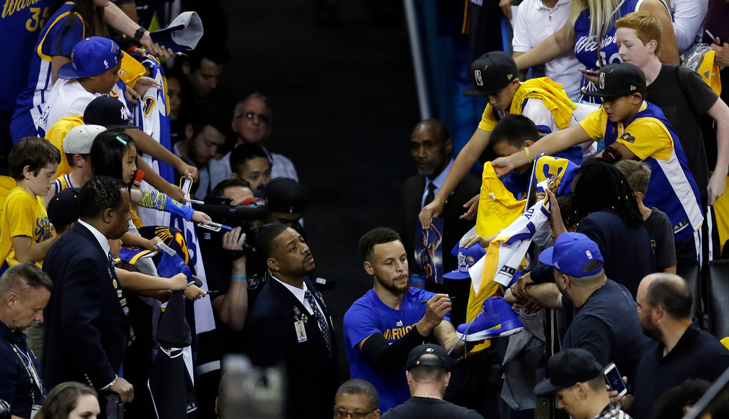 . Golden State Warriors\' Stephen Curry signs autographs after warming up before Game 1 of basketball\'s NBA Finals against the Cleveland Cavaliers Thursday, June 1, 2017, in Oakland, Calif. (AP Photo/Ben Margot)