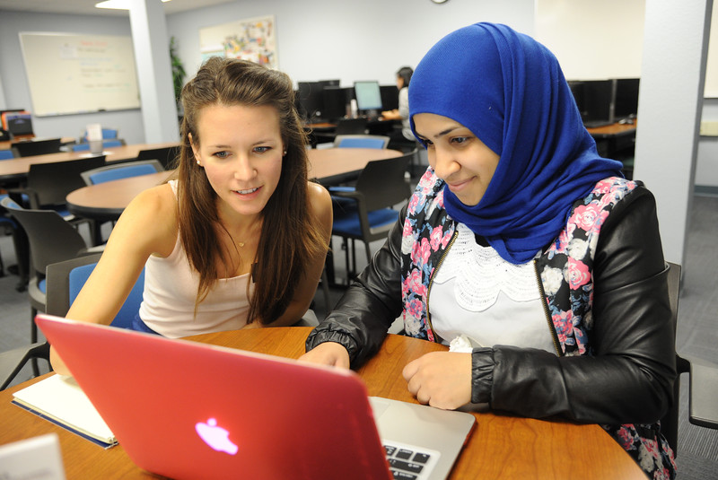 Casa tutor Mary Hood(left) assists student Ruqayh, with her relective essay, Tuesday July 28, 2015.