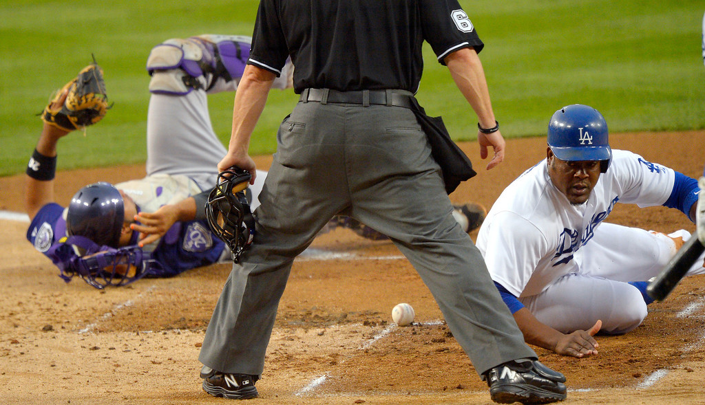 . Los Angeles Dodgers\' Juan Uribe, right, looks around after scoring on a double by Jerry Hairston Jr. after Colorado Rockies catcher Wilin Rosario lost the ball during the second inning of a baseball game, Thursday, July 11, 2013, in Los Angeles. (AP Photo/Mark J. Terrill)