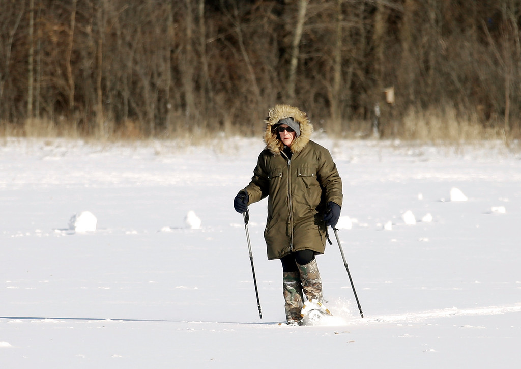 . Chris Gurnick walks past several snow rollers Tuesday, Jan. 28, 2014, in Olmsted Township, Ohio. The National Weather Service has placed most of Ohio under a wind chill warning until Wednesday. (AP Photo/Mark Duncan)