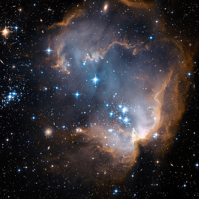 . 2007: NGC 602  This new image taken with NASA\'s Hubble Space Telescope depicts bright, blue, newly formed stars that are blowing a cavity in the center of a star-forming region in the Small Magellanic Cloud.  At the heart of the star-forming region, lies star cluster NGC 602. The high-energy radiation blazing out from the hot young stars is sculpting the inner edge of the outer portions of the nebula, slowly eroding it away and eating into the material beyond. The diffuse outer reaches of the nebula prevent the energetic outflows from streaming away from the cluster. Credit: NASA, ESA, and the Hubble Heritage Team (STScI/AURA) - ESA/Hubble Collaboration